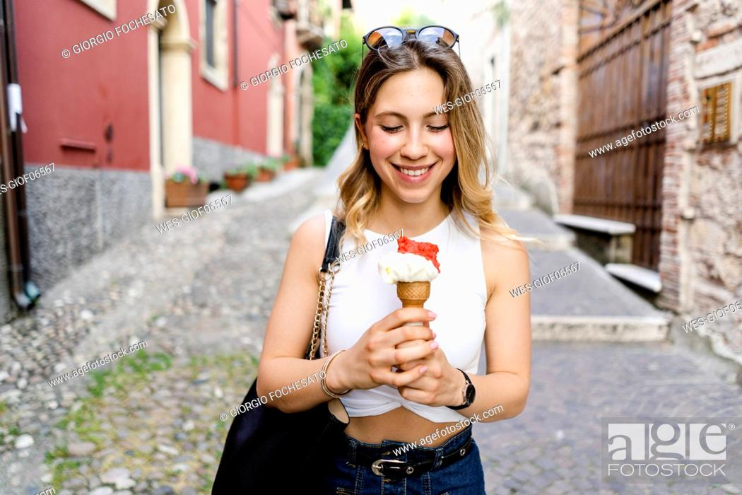 Stock Photo: Portrait of smiling young woman with ice cream cone.