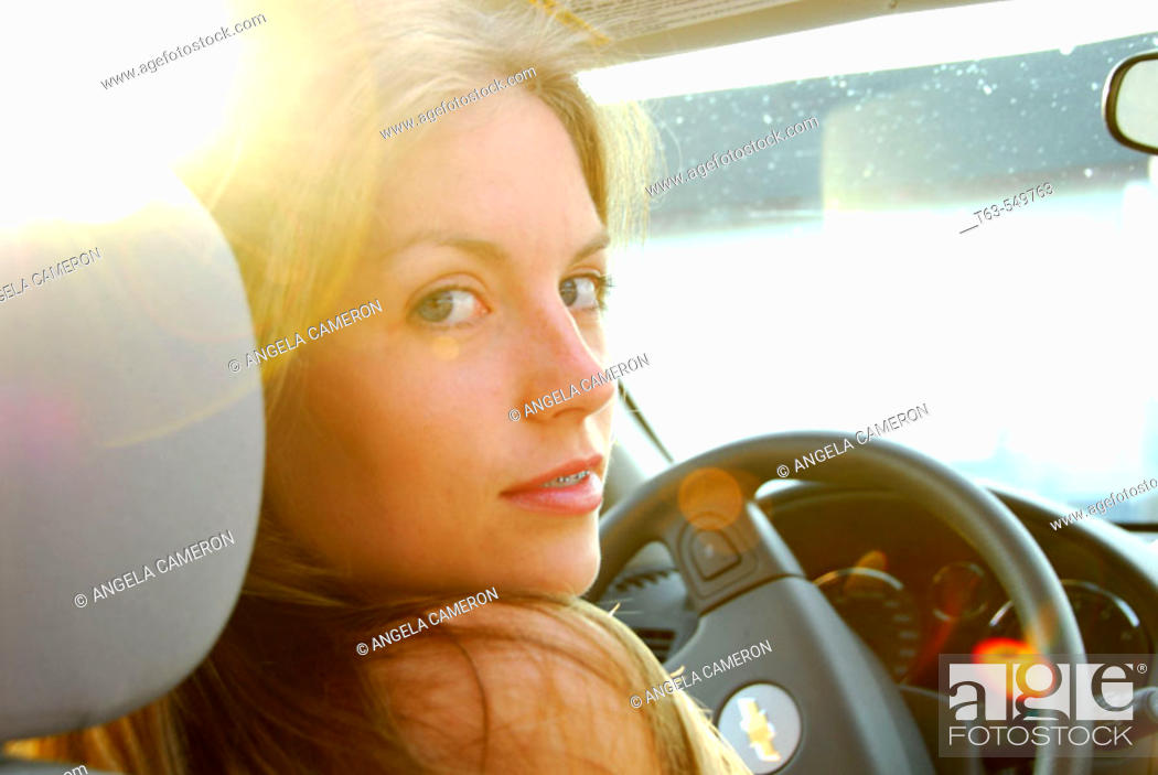 Stock Photo: girl 18 yrs old driving car with evening sun peeking through.