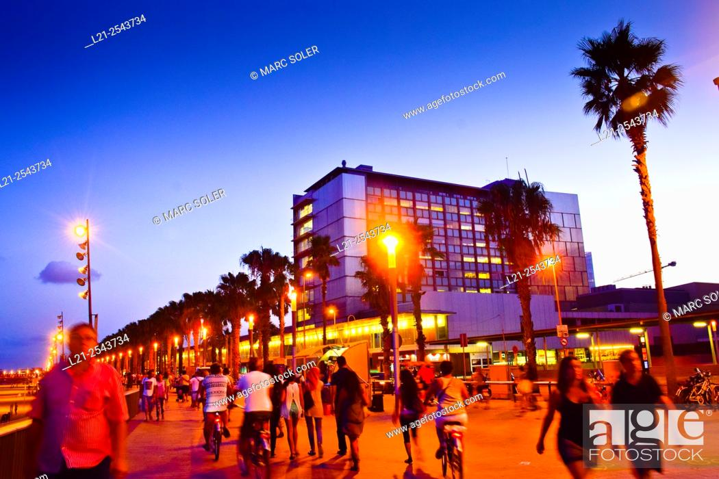 Imagen: People walking along Passeig Maritim at sunset. Hospital del Mar building in background. Barceloneta quarter, Barcelona, Catalonia, Spain.