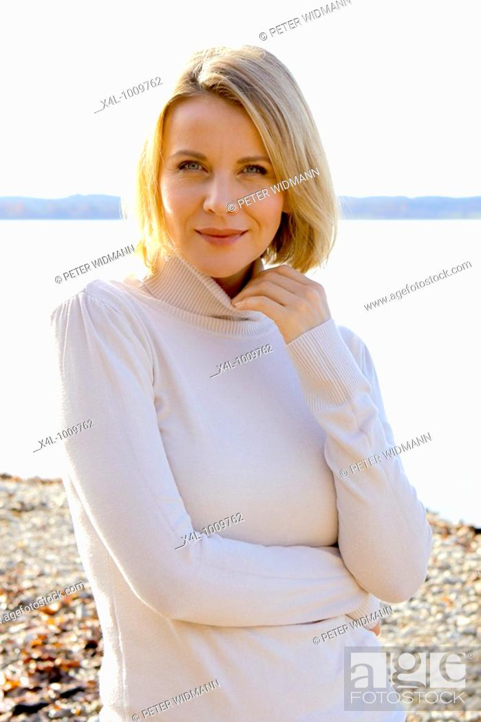 Stock Photo: blonde woman in the late fall at a lake.