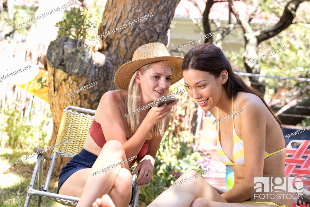 Stock Photo: Two young women in garden sharing cell phone.