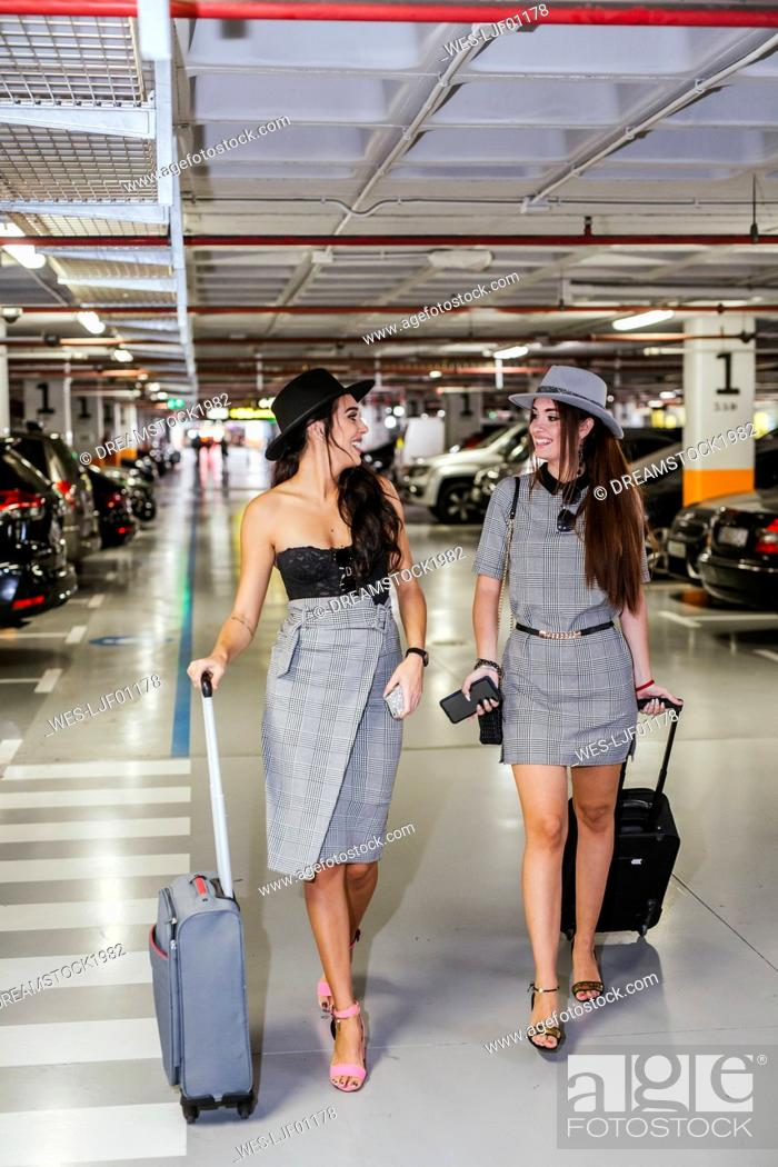 Stock Photo: Two fashionable young women with baggage walking in airport car park.