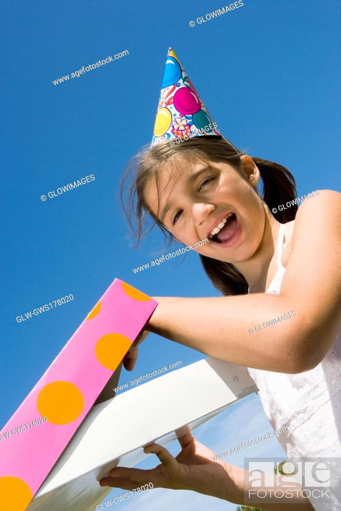Stock Photo: Portrait of a girl opening her birthday present and laughing.