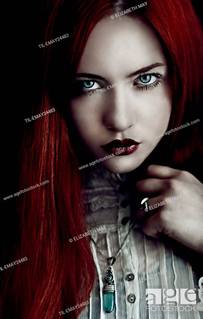 Stock Photo: Close up of young female adult face with long red hair.