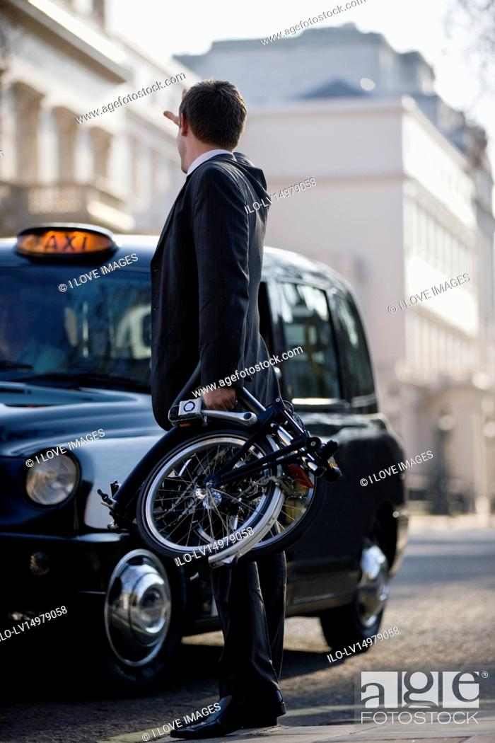 Stock Photo: A businessman hailing a taxi, holding his folded bicycle.