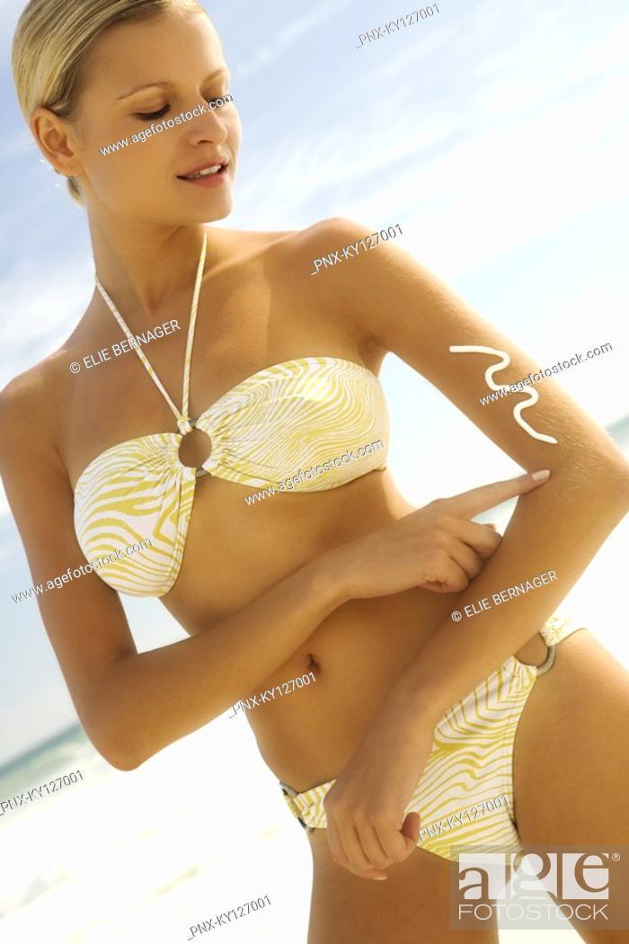 Stock Photo: Young woman in bikini on the beach applying sun cream.