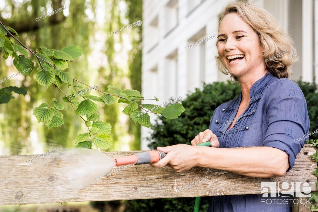 Stock Photo: Mature woman playing with hosepipe in garden.