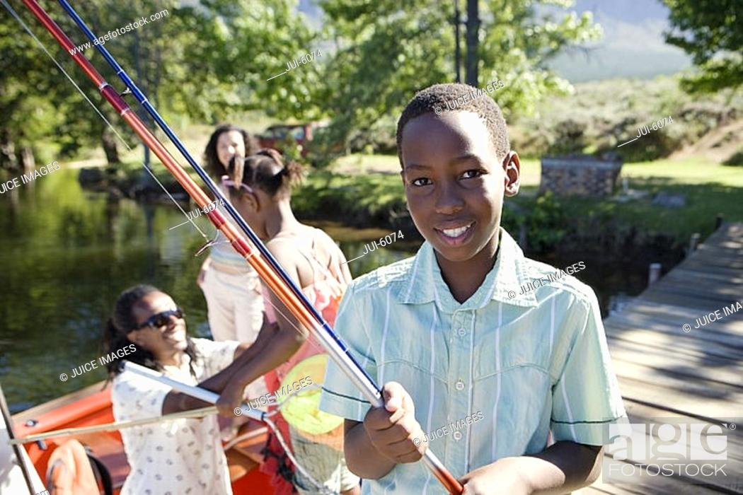Stock Photo: Family standing in motorboat, focus on boy 8-10 standing on lake jetty, holding fishing rod, smiling, portrait.