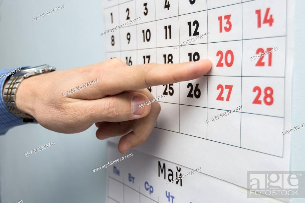 Imagen: The office specialist's hand points to the day off on the wall calendar.