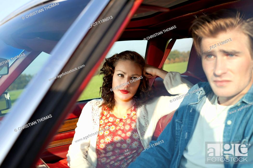 Stock Photo: A pretty rockabilly girl looking at her boyfriend in irritation while sitting in vintage car.