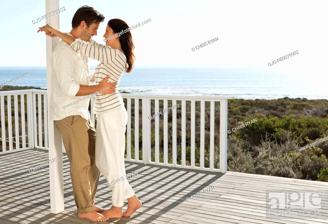 Stock Photo: Smiling couple hugging face to face on patio overlooking ocean.