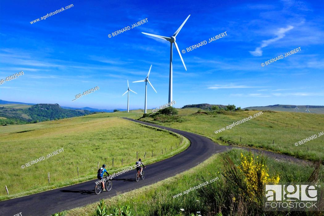 Stock Photo: Cyclists on walk in the Cezallier wind farm, Puy de Dome department, Auvergne Rhone Alpes, France.