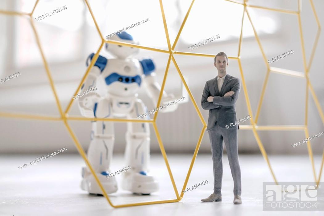 Stock Photo: Miniature businessman figurine standing in front of robot with laptop seperated by structure.