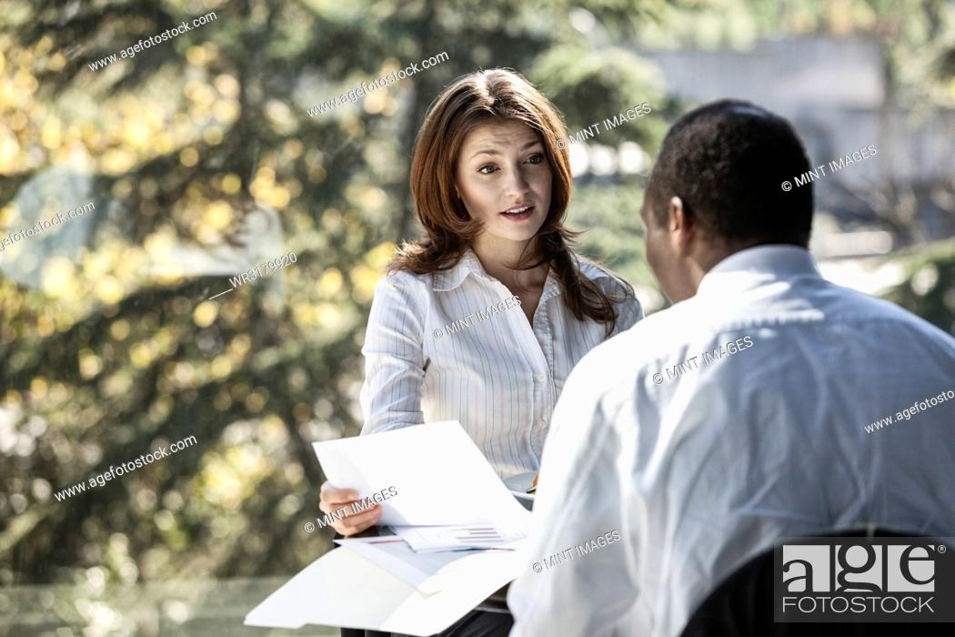 Stock Photo: Caucasian business woman discussing paperwork in a meeting.