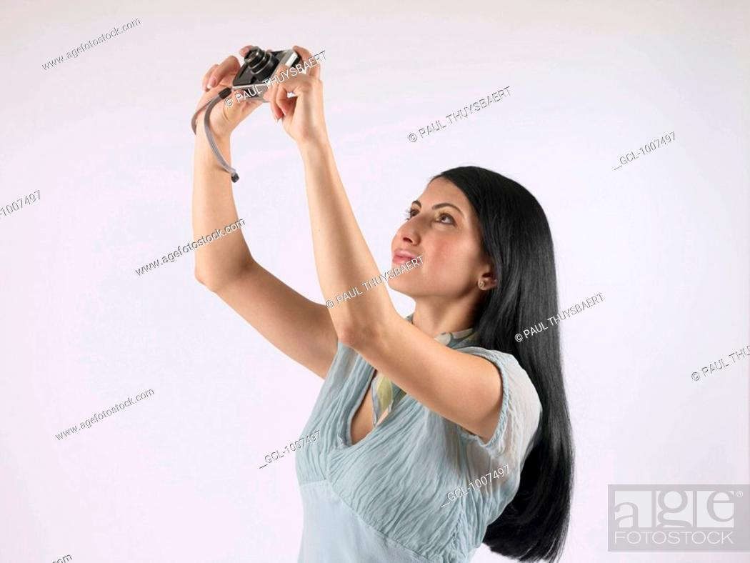 Stock Photo: Woman holding up camera to take pictures.