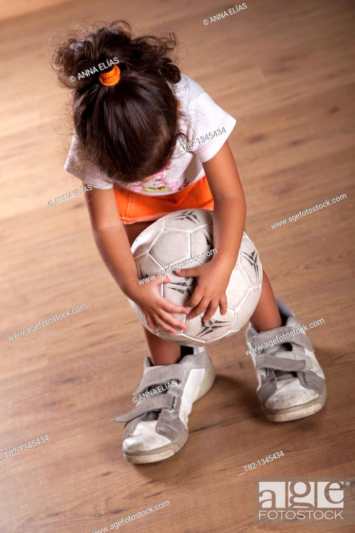 Stock Photo: Three years old little girl playing with a soccer ball with man's sneakers.