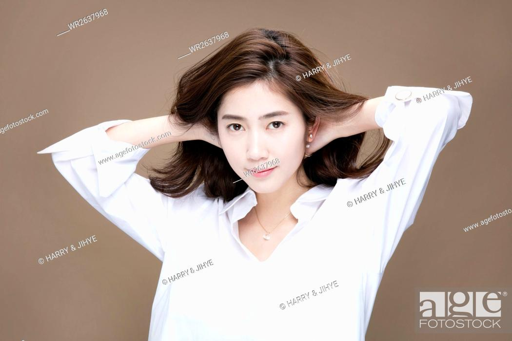 Stock Photo: Portrait of young woman with long wavy hair and in white shirt.