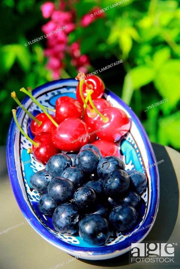Stock Photo: Grosse myrtille bleuet en comparaison avec cerise.