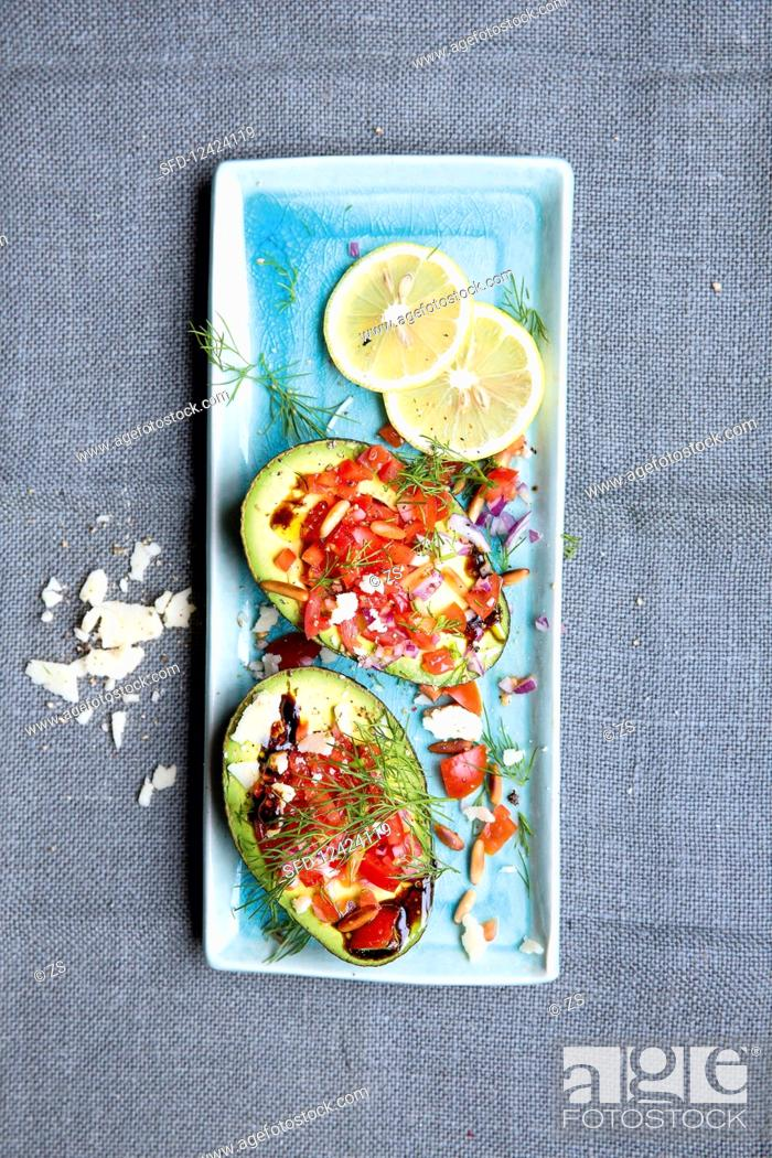 Stock Photo: Avocado filled with tomatoes and shaved Parmesan cheese.