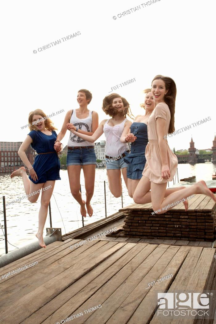 Stock Photo: Five young female friends jumping in the air on a jetty next to the Spree, Berlin, Germany.