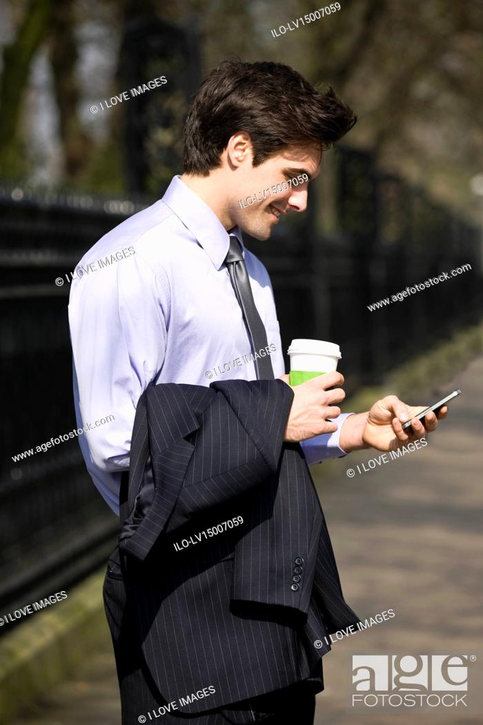 Stock Photo: A businessman holding a hot drink, looking at his mobile phone.