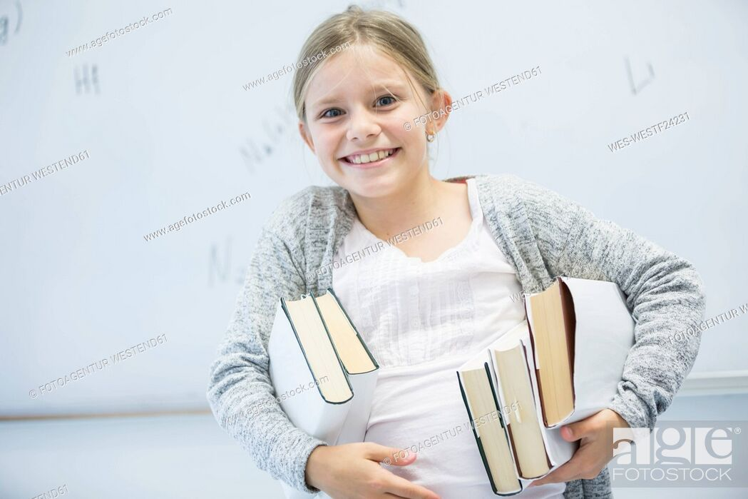 Stock Photo: Portrait of happy schoolgirl carrying books in class.