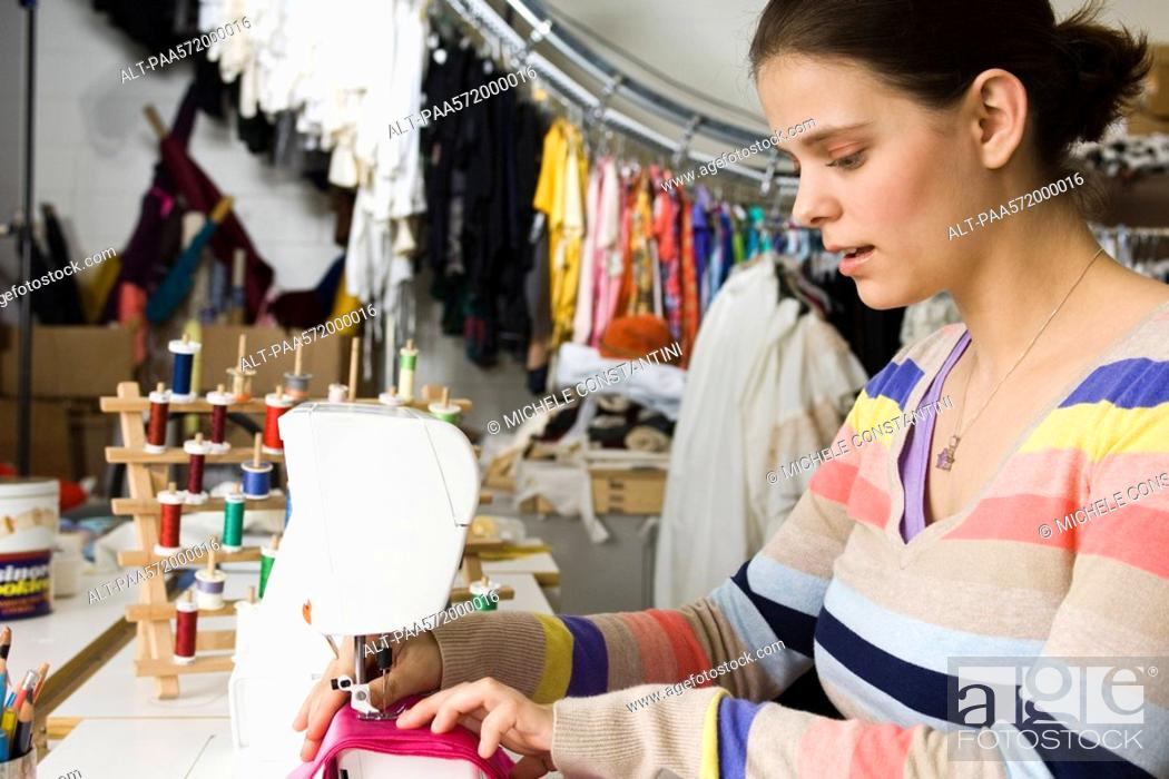 Stock Photo: Seamstress sewing on sewing machine.