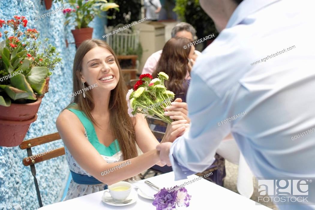 Stock Photo: Man giving bunch of flowers to woman.