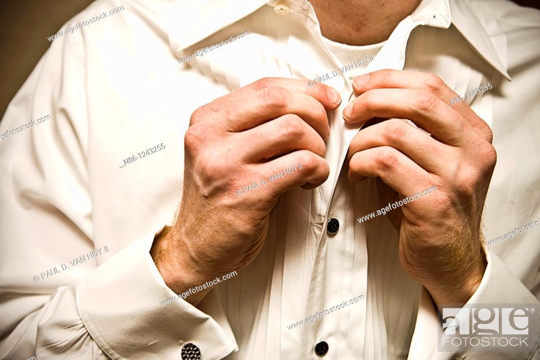 Stock Photo: Man buttoning his shirt.