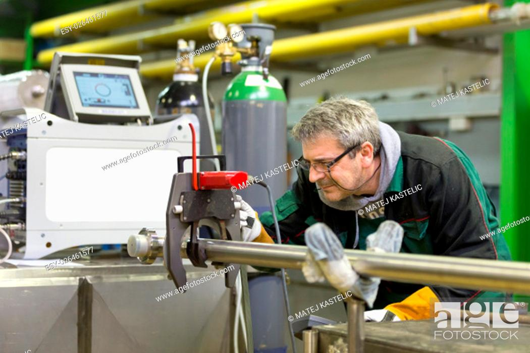 Stock Photo: Industrial operator setting computer controlled process of orbital welding machine in stainless steel pipes manufacturing workshop.
