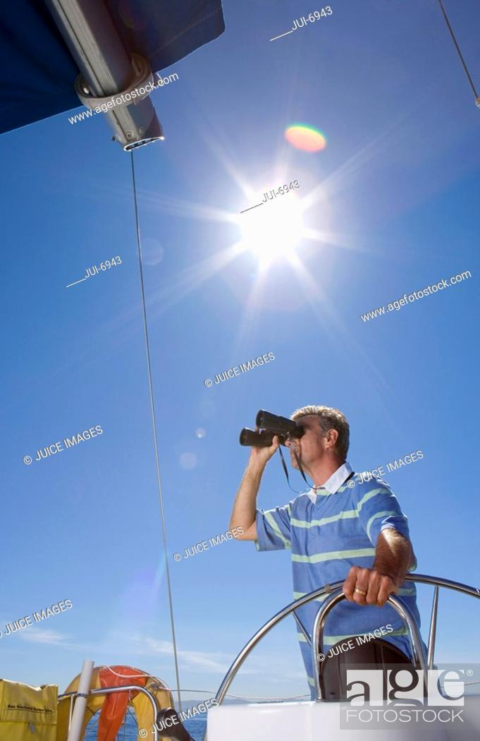 Stock Photo: Man in striped blue polo shirt standing at helm of sailing boat out at sea, looking through binoculars, low angle view lens flare.
