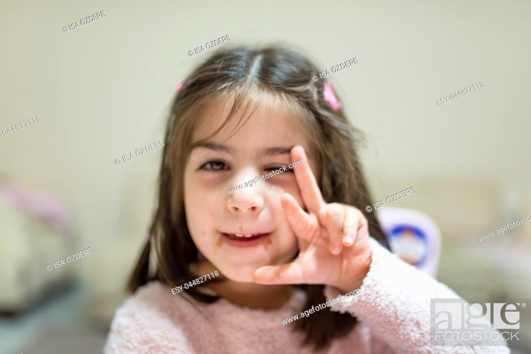 Stock Photo: Little cute girl with dirty funny face after eat surprise chocolate while looking at camera.