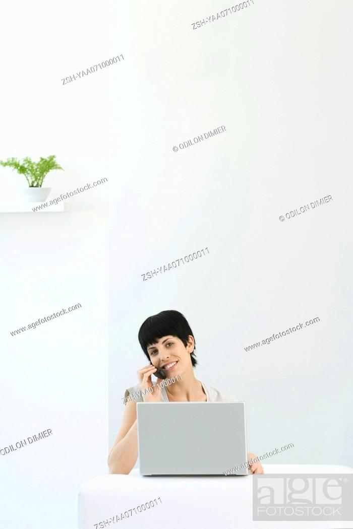 Stock Photo: Woman using laptop computer and cell phone, smiling at camera.