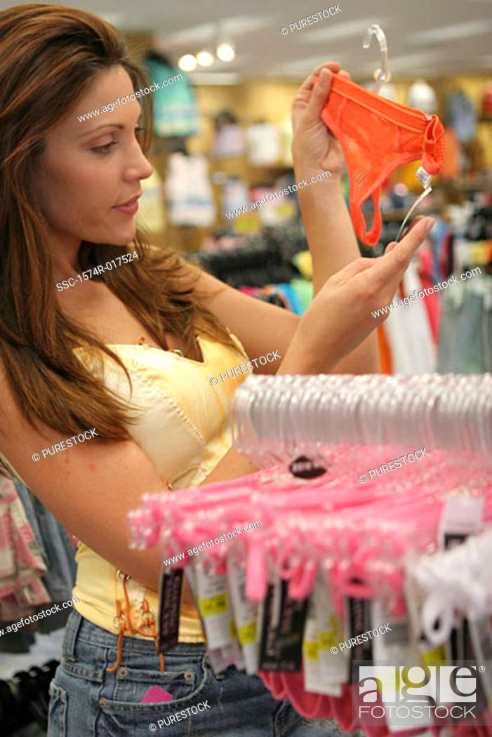 Stock Photo: Side profile of a young woman looking at the price tag of underwear in a clothing store.