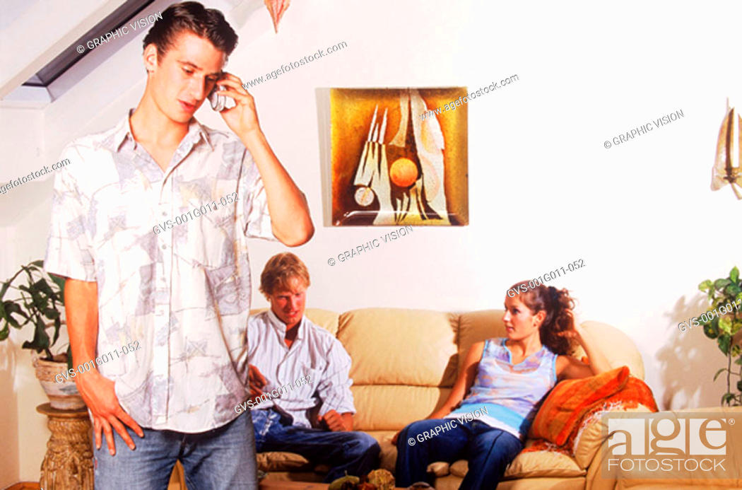 Stock Photo: Young man talking on a mobile phone and a young couple sitting on a sofa.
