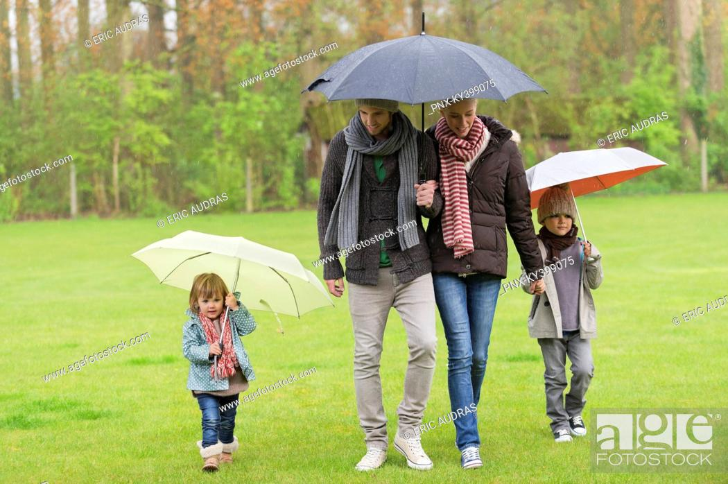 Stock Photo: Family walking with umbrellas in a park.
