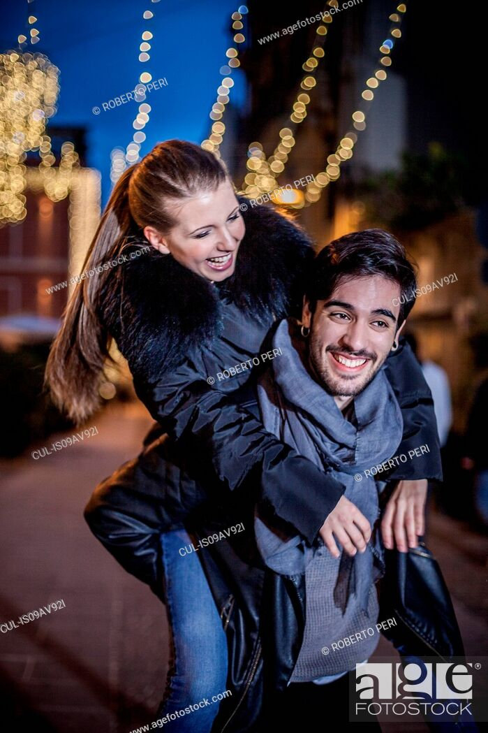 Stock Photo: Young man giving young woman piggyback smiling.