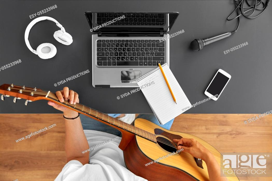 Imagen: young man with laptop playing guitar at table.