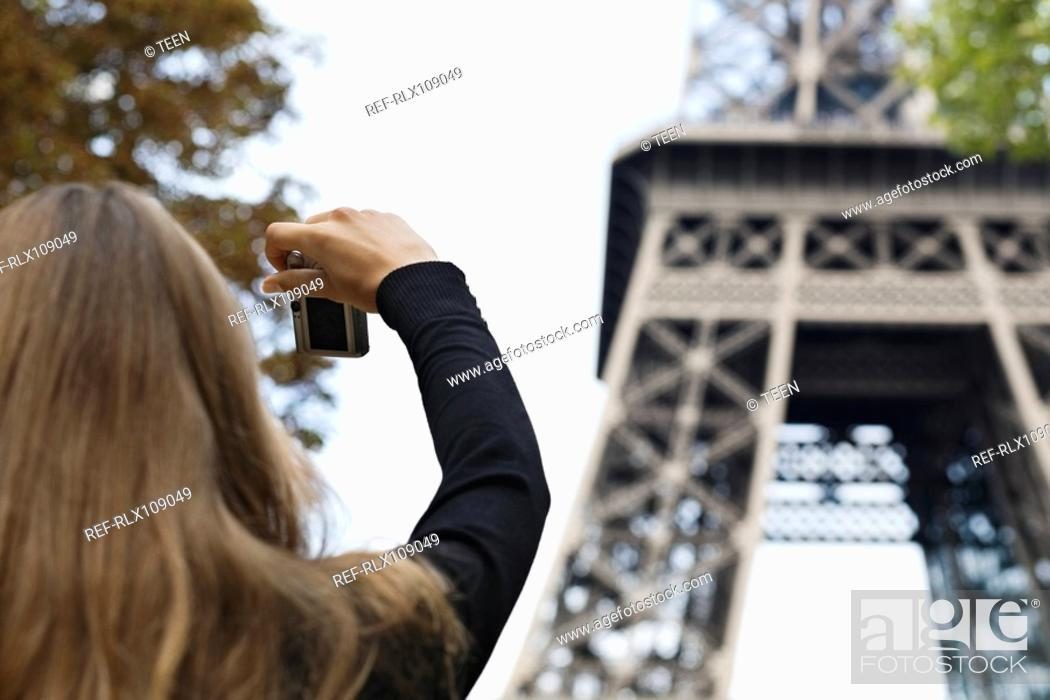 Stock Photo: Young woman taking picture of Eiffel Tower, Paris, France.