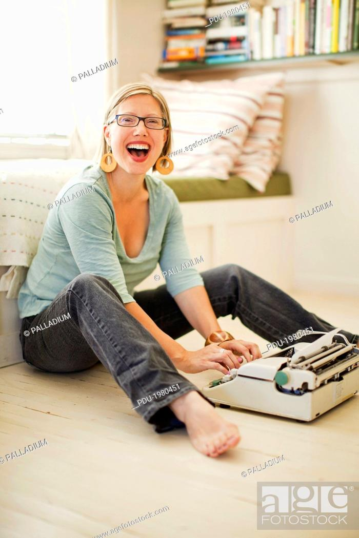 Stock Photo: Woman laughs as she types on her white, antique typewriter that sits on the floor in front of her. Woman is looking at the camera and opening her mouth in.