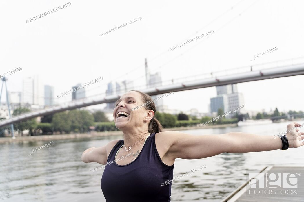 Photo de stock: mid adult sports woman with open arms, enjoying training at riverside Main, in Frankfurt, Germany.