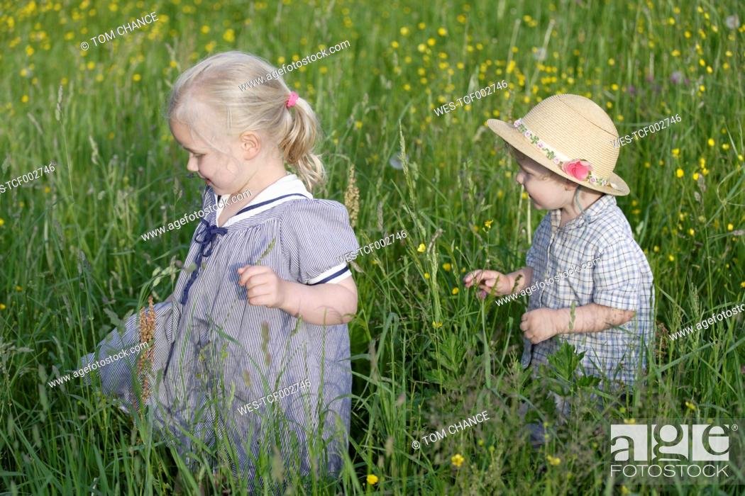 Stock Photo: Germany, Bavaria, Girl and boy walking through meadow.