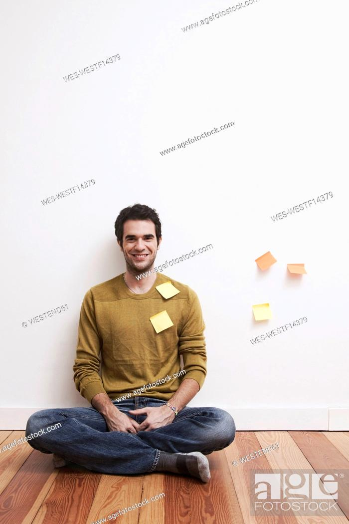 Stock Photo: Men and women sitting aganist wall with adhesive notes.