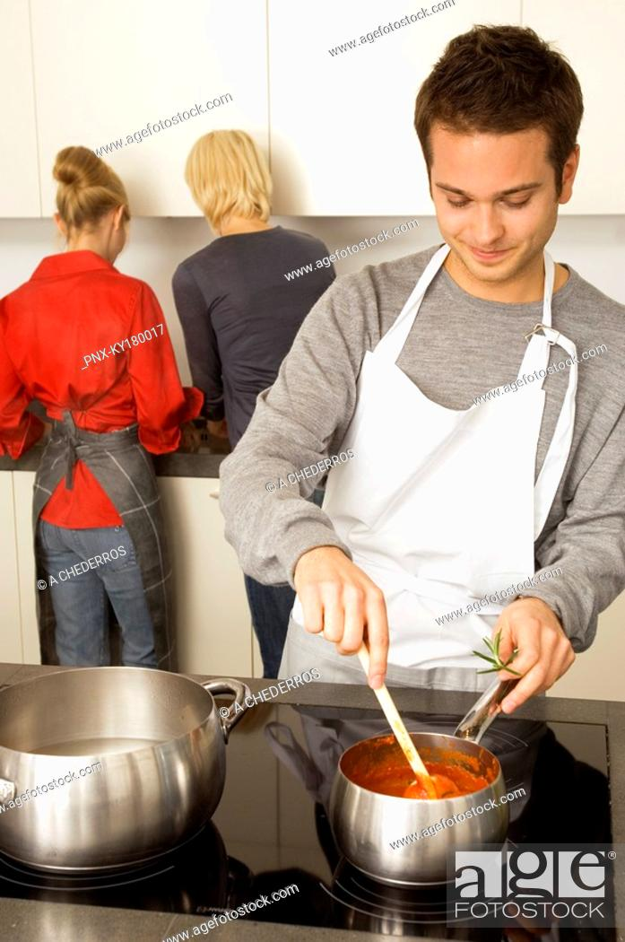 Stock Photo: Young man cooking food and two young women standing behind him in the kitchen.