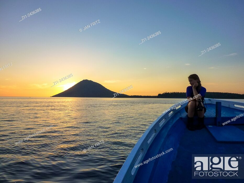 Stock Photo: Gril at boat looking at volcano Manado Tua at sunset in Manado, Sulawesi, Indonesia.