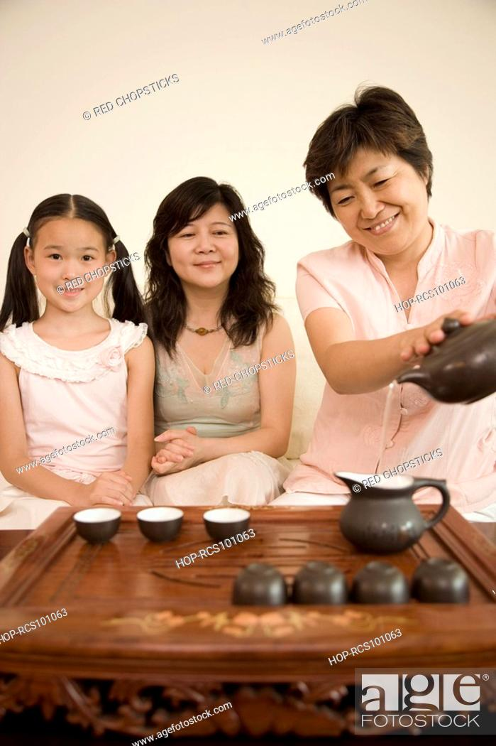 Stock Photo: Mature woman pouring tea into a teapot with another mature woman and her daughter sitting beside her.