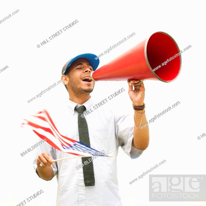 Stock Photo: Hispanic man waving American flag and talking into megaphone.