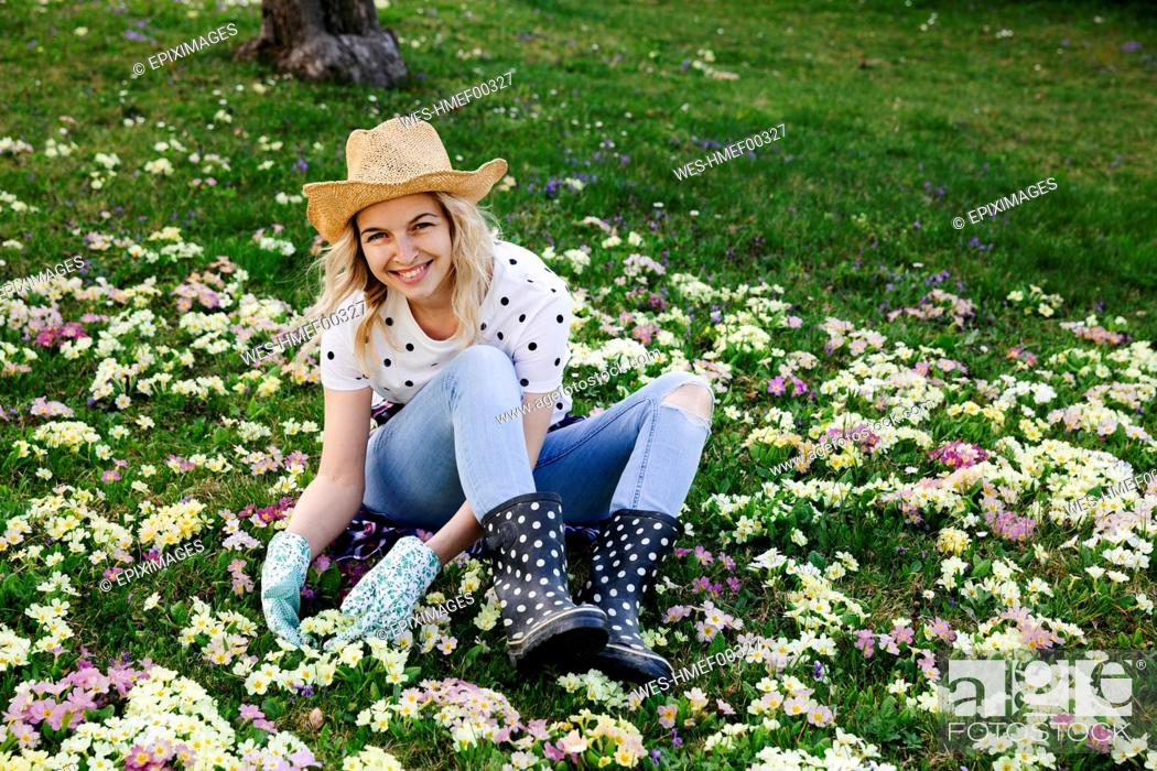 Stock Photo: Young woman is sitting in flower meadow.