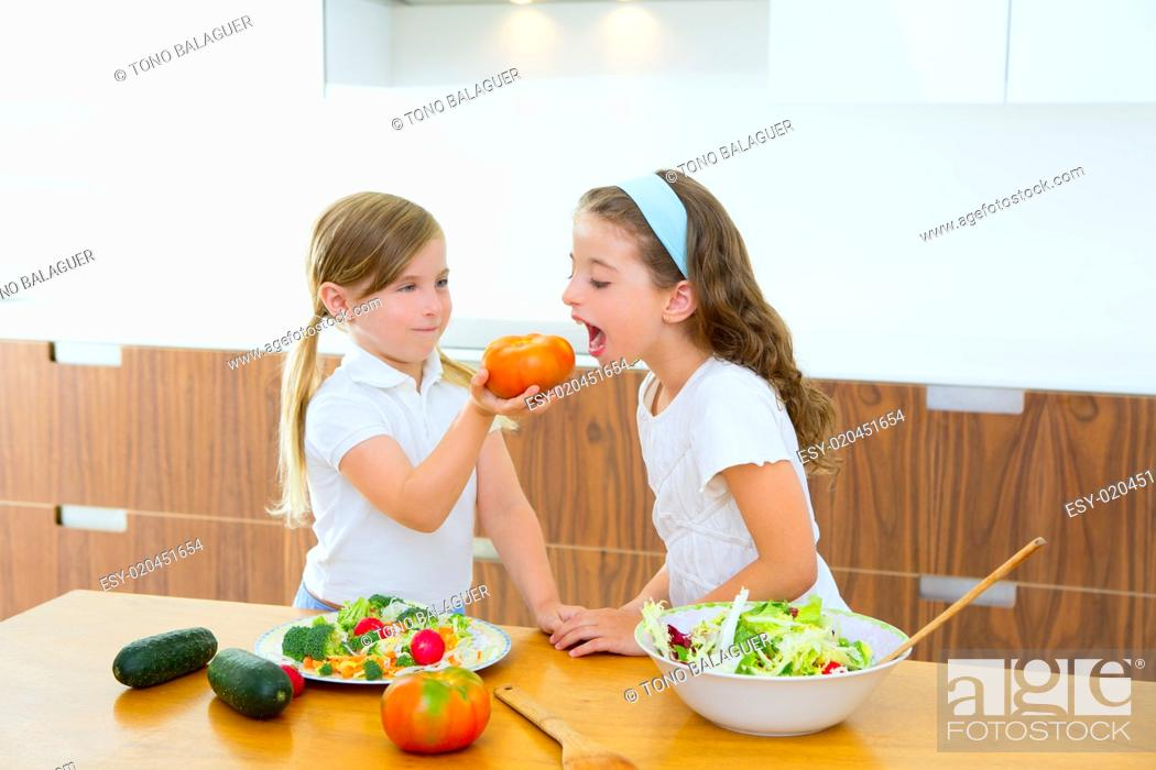 Stock Photo: Beautiful chef sisters at home kitchen preparing salad.