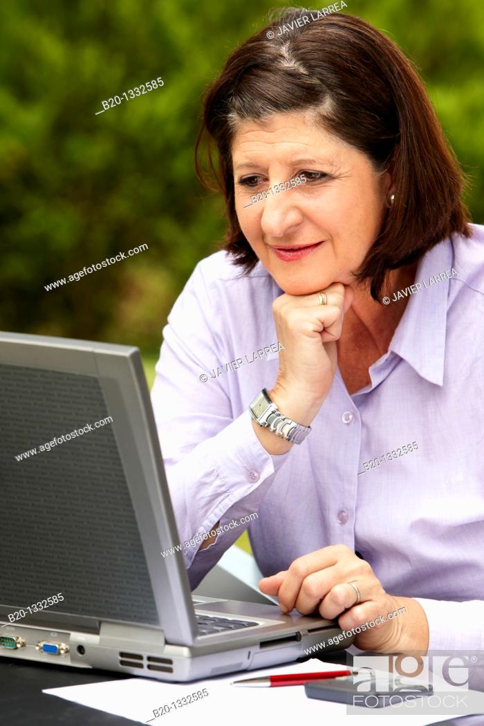 Stock Photo: Retired woman using laptop computer in her garden.